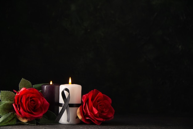Front view of pair of candles red flowers on black
