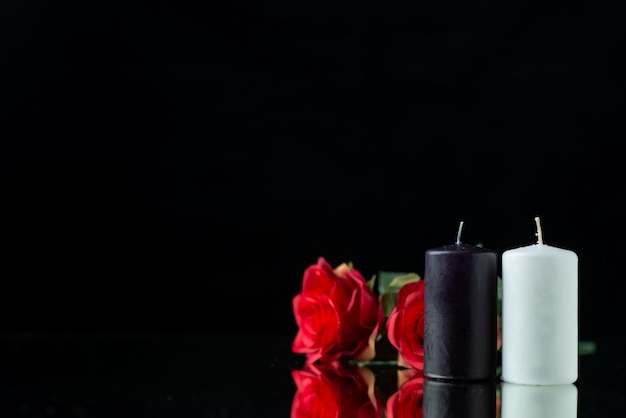 Front view of pair of candles with red roses on black