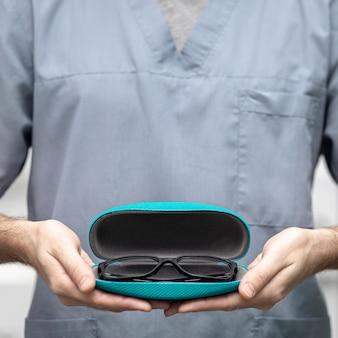 Vista frontale di un paio di occhiali nel caso tenuto dall'uomo