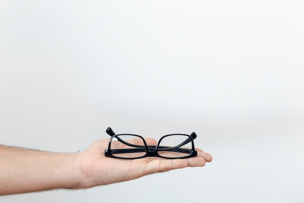 Front view of pair of glasses hand held with copy space