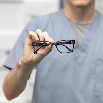 Vista frontale di un paio di occhiali tenuti da uomo sfocato