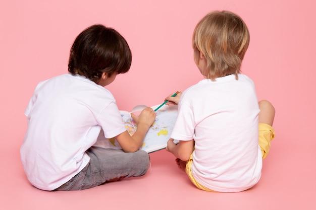 Вид спереди пара мальчиков, рисование карты в белой футболке на розовом