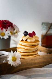 Front view pancake tower with banana and raspberries