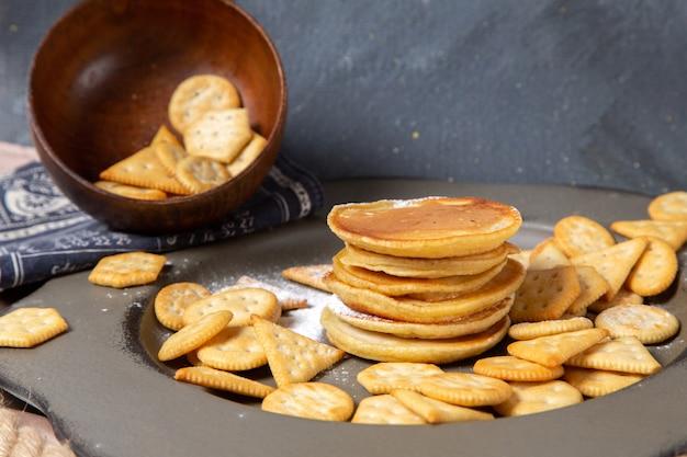 Блины и крекеры вид спереди внутри тарелки на сером