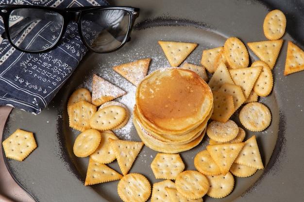 Блины и крекеры с солнцезащитными очками на тарелке, вид спереди