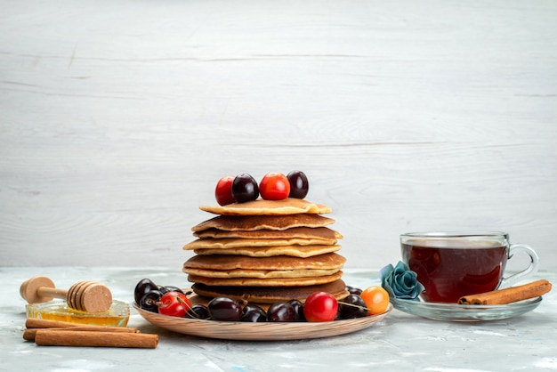 A front view pancakes with cherries inside plate with cinnamon and tea on the dark background fruit cake biscuit bake