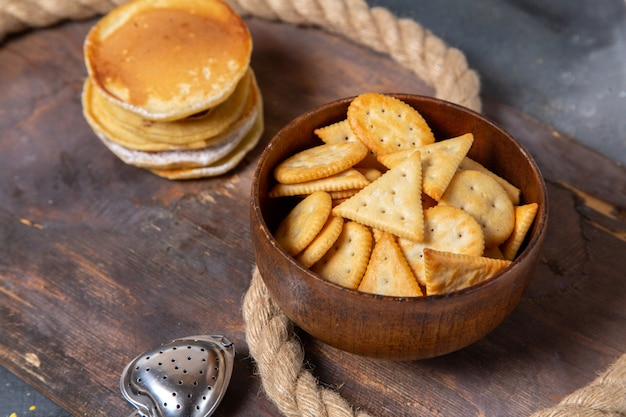Front view pancakes with crisps along with ropes on wooden desk