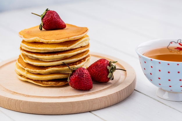 Front view pancakes with strawberries on a tray with a cup of tea