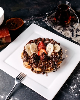 Вид спереди блинов вкусного шоколада вместе с нарезанной красной клубникой и бананами внутри белой тарелки на сером полу