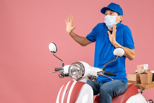 Front view of panicky delivery guy in medical mask wearing hat sitting on scooter on pastel peach background
