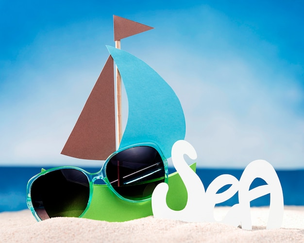 Front view of paper boat on beach with sunglasses