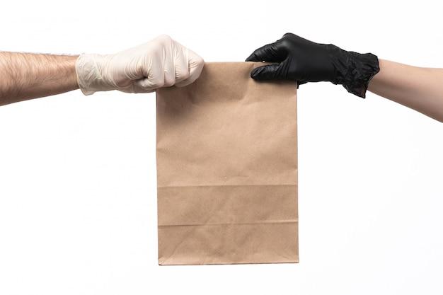Un pacchetto dell'alimento della carta di vista frontale che consegna dalla femmina al maschio su bianco