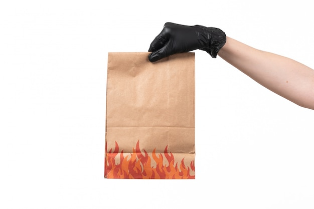 Un pacchetto di carta di vista frontale tiene dalla mano femminile in guanto nero su bianco