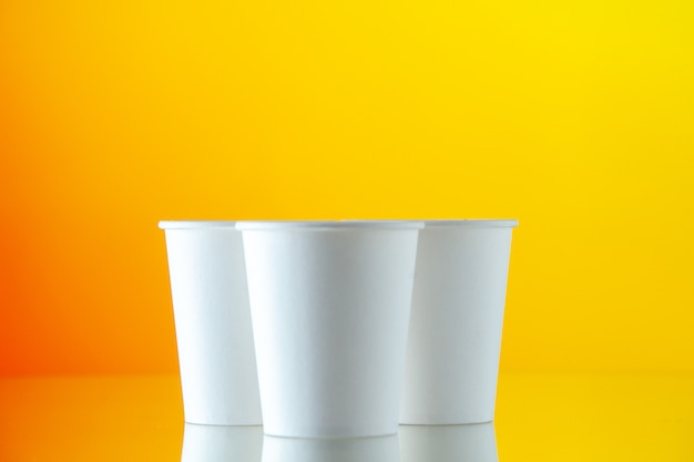 Front view paper water cups on yellow wall