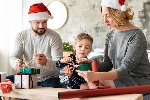 Genitori e bambino di vista frontale che stanno insieme il giorno di natale