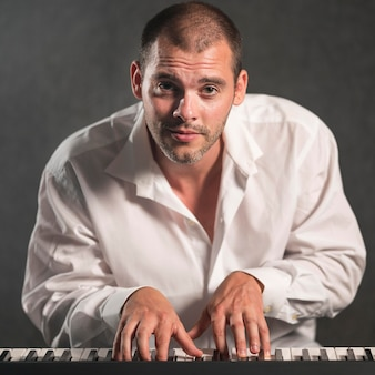Front view passionate man playing keyboards