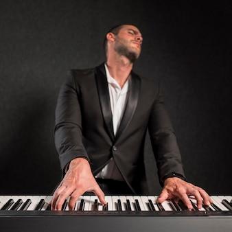 Вид спереди страстный музыкант и его цифровое пианино
