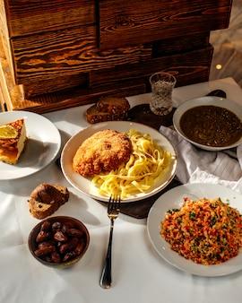 Паста спереди, приготовленная вместе с супом из рубленых овощей и ломтиками хлеба на светлой поверхности