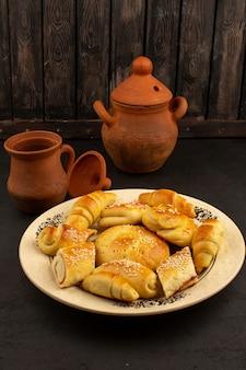 Вид спереди выпечка сладкая коричневая приготовленная внутри белая тарелка на темном