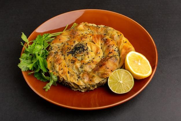 暗い机の上にレモンと茶色のプレートの中に肉のおいしい生地の食事と正面図のペストリー。