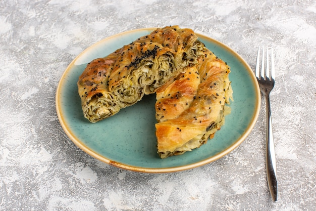 Pasticceria di vista frontale con pasto delizioso della pasta della carne all'interno del piatto affettato sulla scrivania leggera.