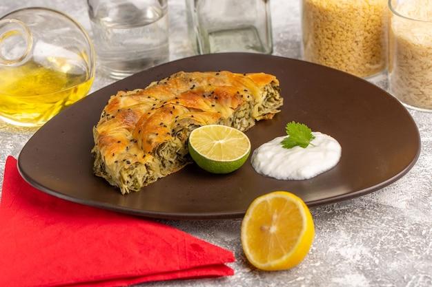 正面図のペストリーと肉のおいしい生地の食事、白いライトデスクにレモンオイルを添えたプレート。