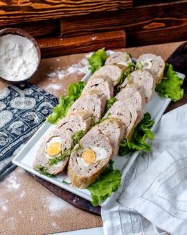 Il patè di vista frontale rotola insieme a insalata verde fresca dentro il piatto bianco sul pavimento marrone