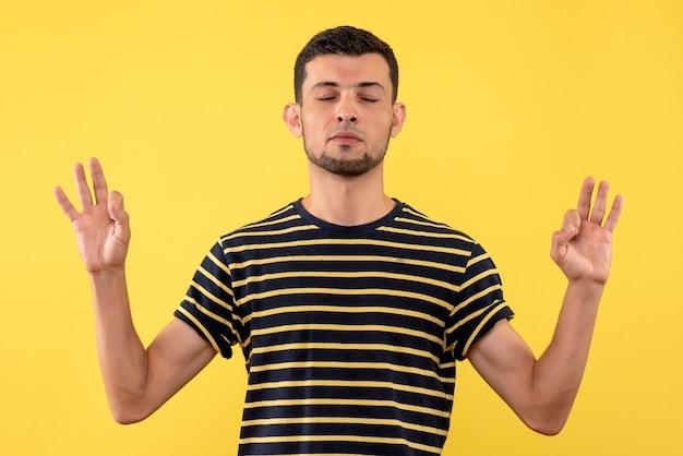 Giovane pacifico di vista frontale nel fondo isolato giallo della maglietta a strisce in bianco e nero