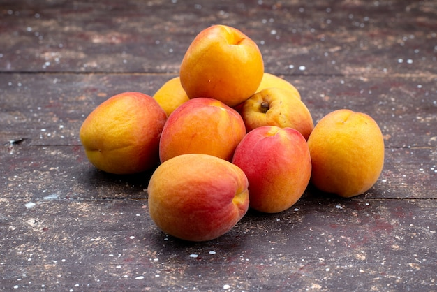 A front view  peaches mellow and juicy on the wooden desk fruit summer pulp