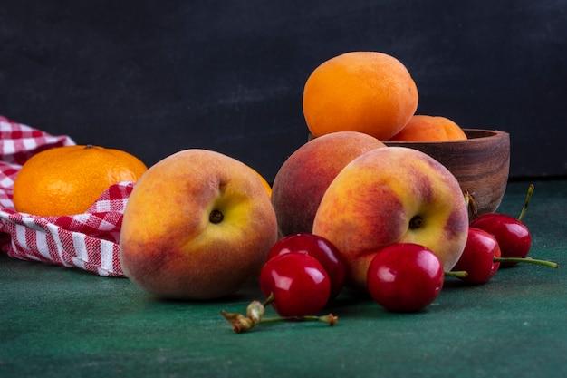 Вид спереди персики с вишней и абрикосами в миску на зеленом