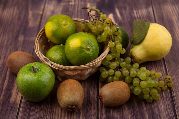 Вид спереди груша с киви, мандаринами, яблоками и виноградом в корзине на деревянной стене