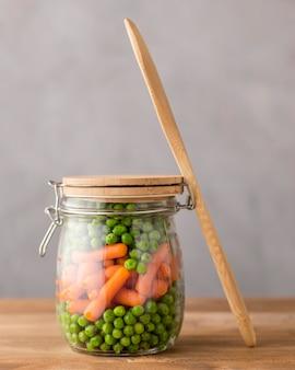 Vista frontale di piselli e carotine in vaso di vetro con cucchiaio