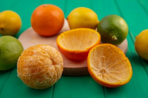 Vista frontale arancia sbucciata con bucce e limoni con limette su sfondo verde