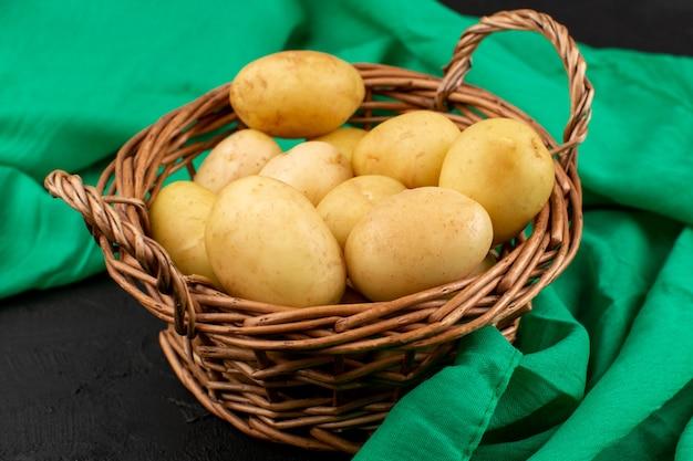 Vista frontale pelate patate all'interno del cestino sul grigio