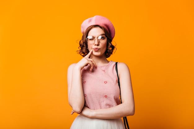 Vista frontale della donna elegante pensierosa in berretto. studio shot di bella ragazza francese in piedi su sfondo giallo.