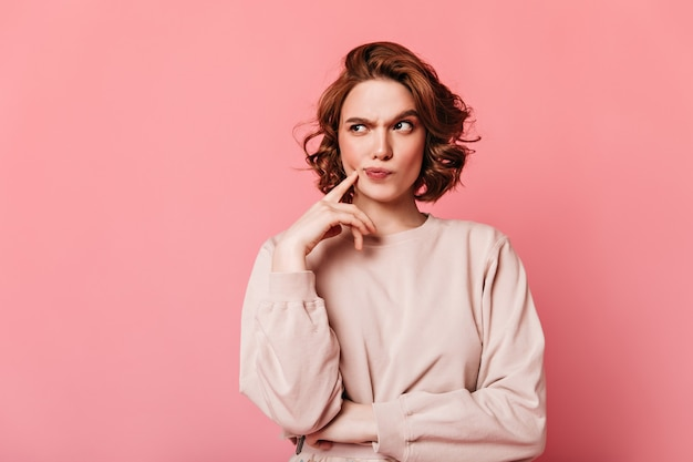 Front view of pensive pretty woman. curly girl thinking on pink background.