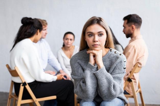 Vista frontale della donna pensosa in una sessione di terapia di gruppo