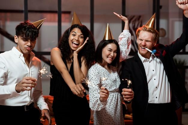 大晦日のパーティーで線香花火を持っている正面図の人々