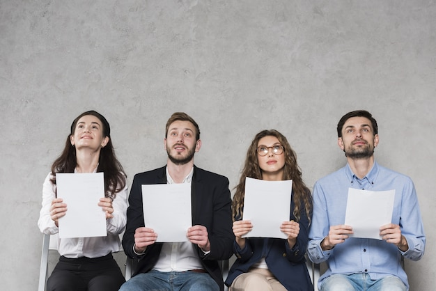 Front view of people waiting for their job interviews holding blank papers with copy space