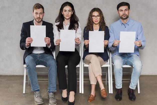 Vista frontale di persone in attesa di colloqui di lavoro in possesso di documenti in bianco