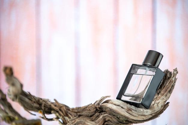 Bottiglia di profumo vista frontale sul ramo di un albero secco isolato su sfondo nudo spazio libero