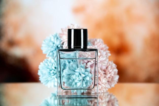 La vista frontale dei fiori della bottiglia di profumo sullo spazio libero del fondo vago marrone beige