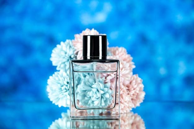 Vista frontale della bottiglia di profumo e dei fiori sullo spazio libero del fondo vago blu