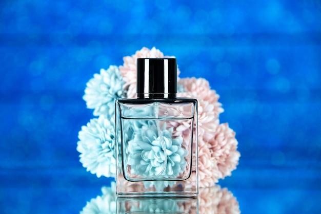 Vista frontale dei fiori della bottiglia di profumo su sfondo blu sfocato stock photo