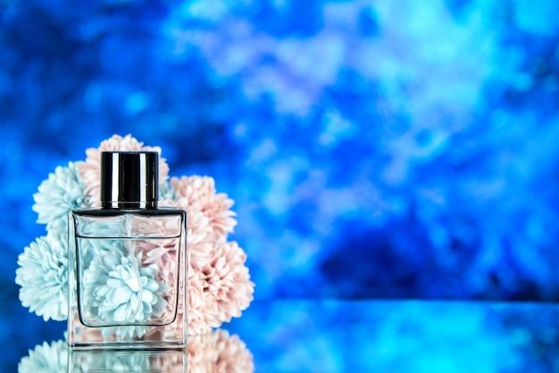 Vista frontale dei fiori della bottiglia di profumo su sfondo sfocato blu con posto libero