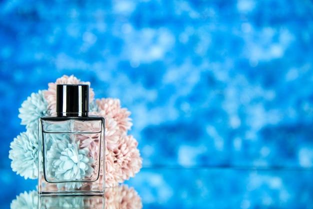 Fiori della bottiglia di profumo di vista frontale su fondo vago blu con spazio libero
