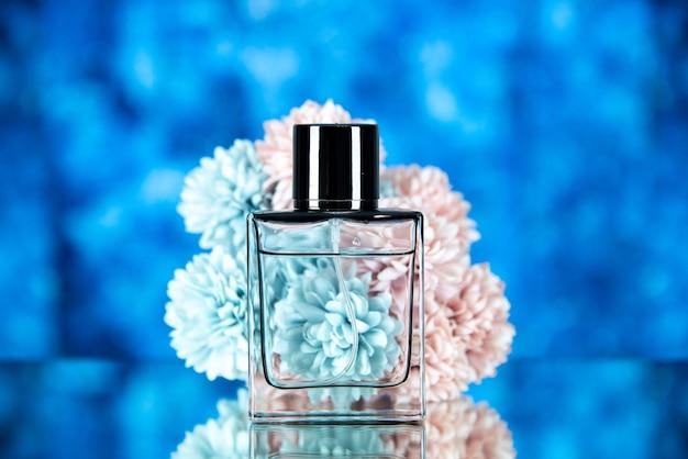 Vista frontale dei fiori della bottiglia di profumo su sfondo sfocato blu