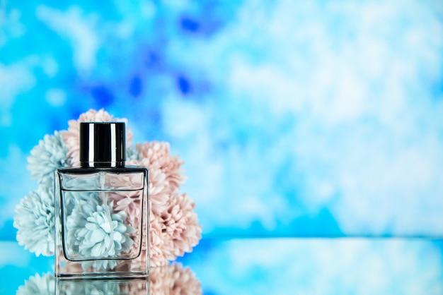 Fiori della bottiglia di profumo di vista frontale sullo spazio libero blu del fondo dell'acquerello