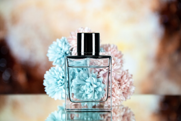 Front view of perfume bottle flowers on brown beige blurred background