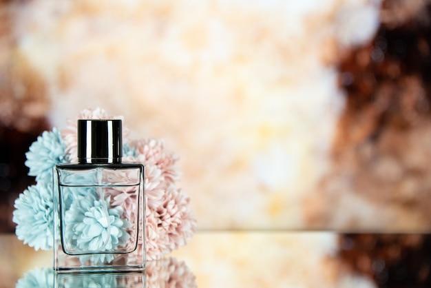 Fiori della bottiglia di profumo di vista frontale sullo spazio libero del fondo vago marrone